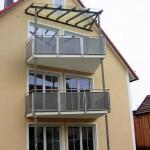 Geländer mit Lochblechfüllung und Überdachung des obersten Balkones