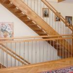 Treppe in Eiche mit Obergurt, vollrundem Handlauf, Pfosten mit Edelstahleinlage
